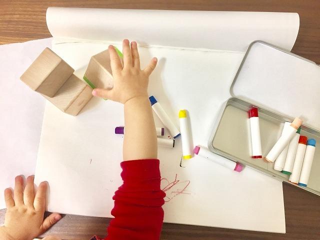 積み木とクレヨンで遊ぶ子供の手