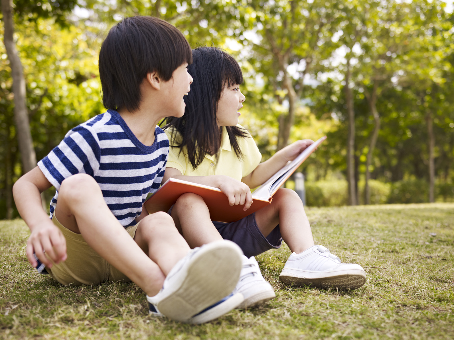 little asian boy and girl with book in hand sitting on grass looking away.